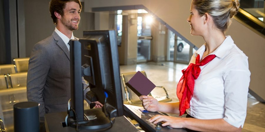 Businessman interacting with female airport staff at the check in desk in airport terminal