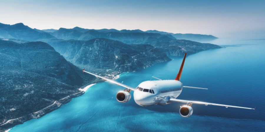 aircraft-is-flying-islands-sea-sunrise-summer-landscape-with-white-passenger-airplane_159067-617