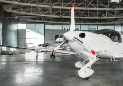 Small private turbo-propeller airplane in hangar, plane on inspection before flight. Air transportation, front view on turboprop plane